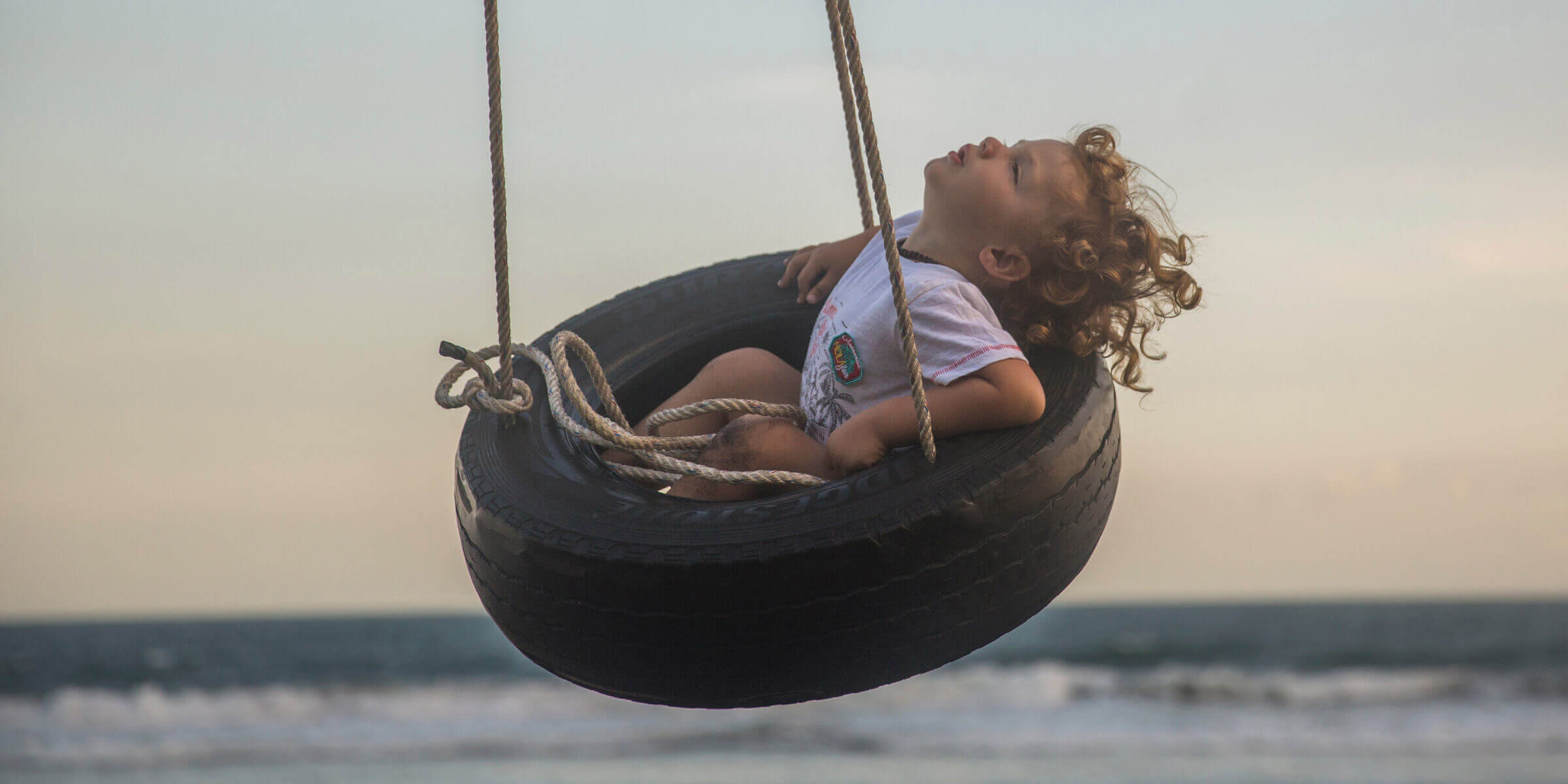 Child on tyre swing at the beach