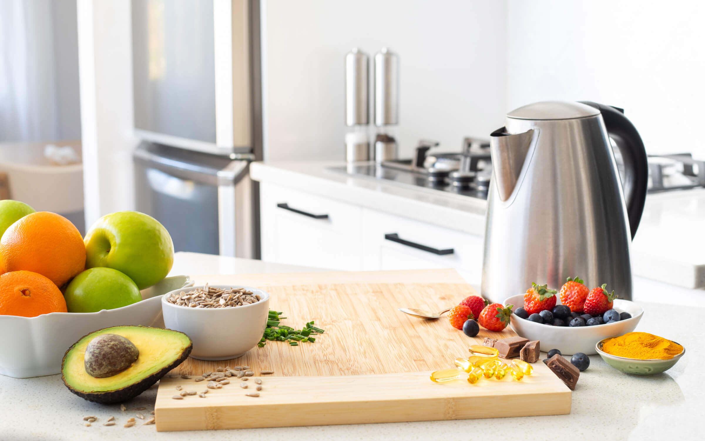 Kitchen setting with kettle, bowl of fruit, seeds, spices and supplement pills