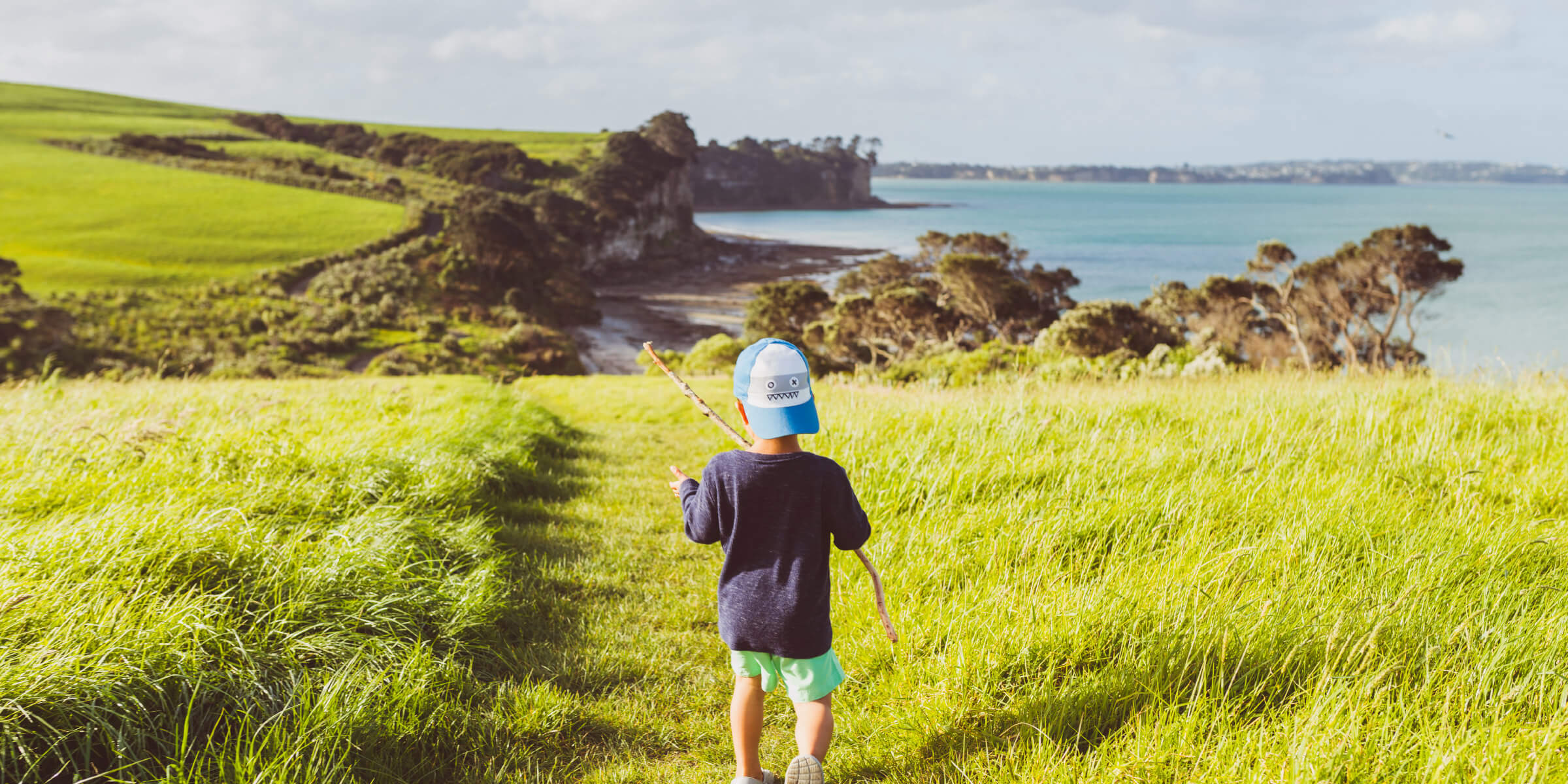 Child walking through park with sea views